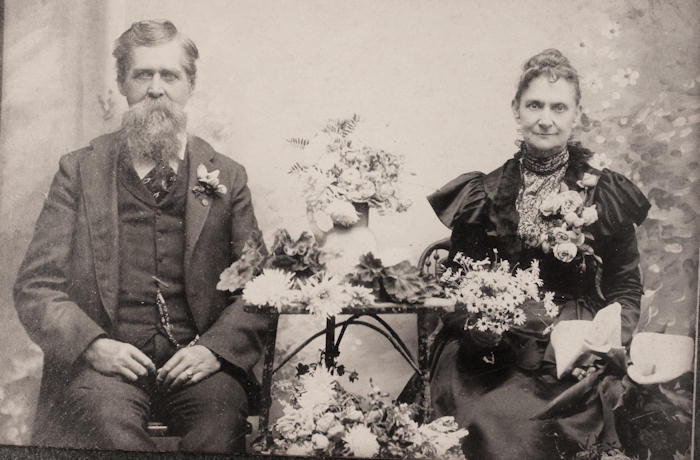 James Clinton Brown and his wife Lucretia/Merticia Tipple Brown. This photo taken Jan 19, 1900 with flowers from their garden.